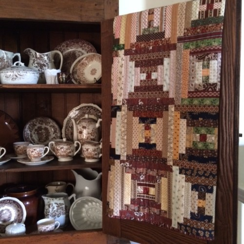 A collection of brown transferware dishes complements this Courthouse Steps quilt