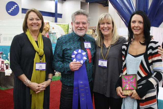 Cheryl Freydberg, Mark Dunn, Lissa Alexander, and Holly Hickman celebrate Moda's Best Booth award. Will the tradition continue?