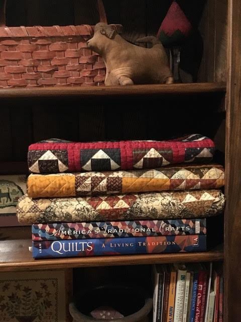 More folded quilts (made by me) in a bookshelf at home.