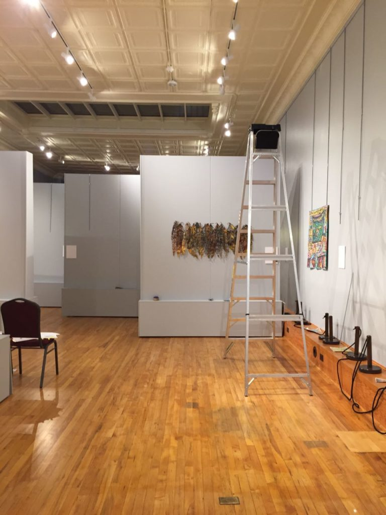 "The first pieces go up. The ""lines"" on the right-hand wall are the hanging rods that will support the art quilts."